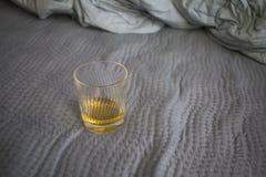 Ένα φλυτζάνι του ουίσκυ στο κρεβάτι στοκ φωτογραφίες με δικαίωμα ελεύθερης χρήσης