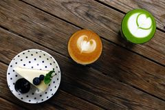 Ένα φλυτζάνι του πράσινου matcha τσαγιού latte και φλυτζάνι του καφέ τέχνης latte Στοκ Φωτογραφίες
