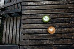 Ένα φλυτζάνι του πράσινου matcha τσαγιού latte και φλυτζάνι του καφέ τέχνης latte Στοκ εικόνα με δικαίωμα ελεύθερης χρήσης