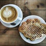 Ένα φλυτζάνι του cappuccino με τα περίπλοκα σχέδια του αφρού και croissants γεμισμένος σε έναν πίνακα των κατά προσέγγιση αντιμετ στοκ εικόνα