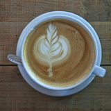 Ένα φλυτζάνι του cappuccino με τα περίπλοκα σχέδια αφρού σε έναν πίνακα των κατά προσέγγιση αντιμετωπισμένων πινάκων στοκ φωτογραφία με δικαίωμα ελεύθερης χρήσης