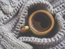Ένα φλυτζάνι του espresso σε ένα χειμερινό πουλόβερ Η έννοια της εγχώριων άνεσης, του coziness και της ζεστασιάς Στοκ Φωτογραφία