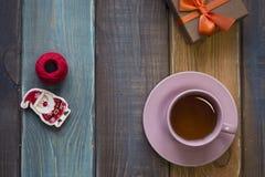 Ένα φλυτζάνι τσαγιού, santa παιχνιδιών, νηματόδεμα των νημάτων και ένα κιβώτιο δώρων Στοκ Εικόνες