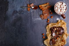 Ένα φλυτζάνι marshmallow στη σοκολάτα, ραβδιά κανέλας, κουτάλια στη σοκολάτα, το κέικ και τα φουντούκια επάνω από την όψη Στοκ Εικόνες