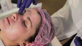 Ένα φορημένο γάντια χέρι παίρνει μια κατευναστική κρέμα στο πρόσωπο γυναικών ` s Κοκκινισμένο, ενοχλημένο δέρμα μετά από mesother απόθεμα βίντεο