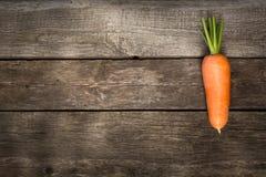 Ένα φρέσκο οργανικό καρότο στον ξύλινο πίνακα διάστημα αντιγράφων Στοκ Εικόνες