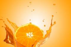 Ένα φρέσκο, juicy και νόστιμο πορτοκάλι που προκαλεί τον παφλασμό νερού προς όλες τις κατευθύνσεις Πορτοκαλί υπόβαθρο χρώματος στοκ φωτογραφία