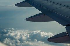 Ένα φτερό αεροπλάνων μέσω του παραθύρου αεροπλάνων με έναν νεφελώδη ουρανό Στοκ φωτογραφία με δικαίωμα ελεύθερης χρήσης