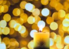 Ένα φως κεριών στο κίτρινο υπόβαθρο bokeh Στοκ εικόνα με δικαίωμα ελεύθερης χρήσης