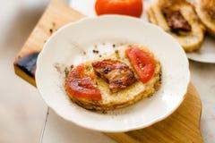 Ένα φωτεινό και εύγευστο φρέσκο τηγανισμένο καυτό σάντουιτς με τα αυγά, τις φέτες μπέϊκον και ντοματών στο ψωμί στοκ φωτογραφία με δικαίωμα ελεύθερης χρήσης