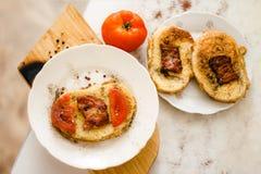 Ένα φωτεινό και εύγευστο φρέσκο τηγανισμένο καυτό σάντουιτς με τα αυγά, τις φέτες μπέϊκον και ντοματών στο ψωμί στοκ εικόνα