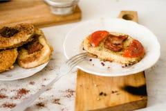 Ένα φωτεινό και εύγευστο φρέσκο τηγανισμένο καυτό σάντουιτς με τα αυγά, τις φέτες μπέϊκον και ντοματών στο ψωμί στοκ φωτογραφίες με δικαίωμα ελεύθερης χρήσης