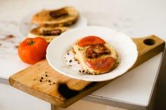 Ένα φωτεινό και εύγευστο φρέσκο τηγανισμένο καυτό σάντουιτς με τα αυγά, τις φέτες μπέϊκον και ντοματών στο ψωμί στοκ εικόνες
