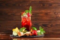Ένα φωτεινό κόκκινο ποτό θερινού οινοπνεύματος με τα μούρα, τον ασβέστη, τη μέντα, και το βερμούτ σε ένα καφετί ξύλινο υπόβαθρο δ Στοκ εικόνες με δικαίωμα ελεύθερης χρήσης