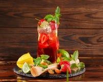 Ένα φωτεινό κόκκινο ποτό θερινού οινοπνεύματος με τα μούρα, τον ασβέστη, τη μέντα, και το βερμούτ σε ένα καφετί ξύλινο υπόβαθρο δ Στοκ φωτογραφίες με δικαίωμα ελεύθερης χρήσης
