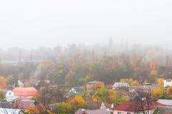 Ένα φωτεινό τοπίο φθινοπώρου με τα ζωηρόχρωμες δέντρα και τις στέγες Στοκ Φωτογραφία
