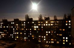 Ένα φωτεινό φεγγάρι πέρα από το σπίτι, με τα φωτεινά παράθυρα Στοκ εικόνα με δικαίωμα ελεύθερης χρήσης