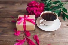 Ένα φλιτζάνι του καφέ, ένα κόκκινα σχέδιο peonies και ένα κιβώτιο δώρων στο ξύλινο υπόβαθρο παλαιά επιχειρησιακού καφέ συμβάσεων  Στοκ φωτογραφία με δικαίωμα ελεύθερης χρήσης