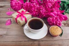 Ένα φλιτζάνι του καφέ, ένα ρόδινα σχέδιο peonies και ένα κιβώτιο δώρων στο ξύλινο υπόβαθρο παλαιά επιχειρησιακού καφέ συμβάσεων δ Στοκ φωτογραφία με δικαίωμα ελεύθερης χρήσης