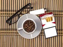 Ένα φλιτζάνι του καφέ, γυαλιά και ένα ελαφρύτερο πακέτο των τσιγάρων Στοκ Φωτογραφίες