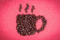 Ένα φλιτζάνι του καφέ κάνει από τα φασόλια καφέ στο κόκκινο υπόβαθρο υφασμάτων Στοκ εικόνες με δικαίωμα ελεύθερης χρήσης