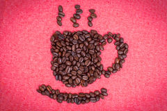Ένα φλιτζάνι του καφέ κάνει από τα φασόλια καφέ στο κόκκινο υπόβαθρο υφασμάτων Στοκ Εικόνες
