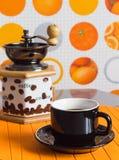 Ένα φλιτζάνι του καφέ και ένας μύλος σε ένα πορτοκαλί υπόβαθρο Στοκ Φωτογραφίες