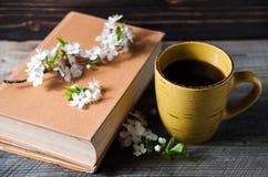 Ένα φλιτζάνι του καφέ και ένα βιβλίο στο ξύλινο υπόβαθρο με το καλό λουλούδι Στοκ Εικόνες