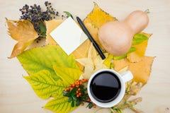 Ένα φλιτζάνι του καφέ και μια σημείωση με την ανθοδέσμη των φύλλων, των μούρων και των σπόρων φθινοπώρου Στοκ φωτογραφία με δικαίωμα ελεύθερης χρήσης