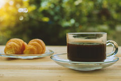 Ένα φλιτζάνι του καφέ και croissants στο θολωμένο πράσινο φυσικό υπόβαθρο Στοκ Εικόνες