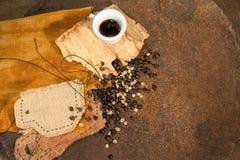 Ένα φλιτζάνι του καφέ με τα παλαιά φασόλια ξύλου και καφέ στη σκουριασμένη σύσταση Στοκ Φωτογραφία