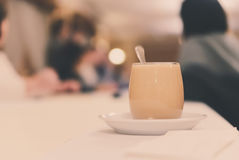 Ένα φλιτζάνι του καφέ με το γάλα σε έναν μακρύ πίνακα Στοκ Εικόνες