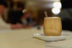 Ένα φλιτζάνι του καφέ με το γάλα σε έναν μακρύ πίνακα Στοκ φωτογραφία με δικαίωμα ελεύθερης χρήσης