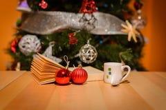 Ένα φλιτζάνι του καφέ πίσω από το χριστουγεννιάτικο δέντρο στοκ εικόνες