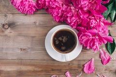 Ένα φλιτζάνι του καφέ, ρόδινο σχέδιο peonies στο ξύλινο υπόβαθρο παλαιά επιχειρησιακού καφέ συμβάσεων διαμορφωμένη φλυτζάνι φρέσκ Στοκ Εικόνες