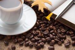 Ένα φλιτζάνι του καφέ Σημειωματάριο και πέννα Φασόλια καφέ στον πίνακα Στοκ Εικόνες