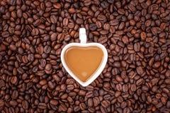 Ένα φλιτζάνι του καφέ στα φασόλια καφέ Στοκ εικόνα με δικαίωμα ελεύθερης χρήσης