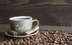 Ένα φλιτζάνι του καφέ, τα φασόλια καφέ και τα ραβδιά κανέλας αποφλοιώνουν Στοκ Εικόνες