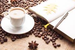 Ένα φλιτζάνι του καφέ, ψημένα φασόλια καφέ, σημειωματάριο, μάνδρα Στοκ εικόνες με δικαίωμα ελεύθερης χρήσης