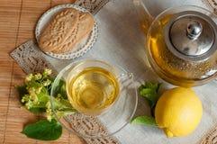 Ένα φλυτζάνι γυαλιού του τσαγιού λουλουδιών ασβέστη και τα μπισκότα σε μια ξύλινη επιφάνεια με ένα λινό δένουν την πετσέτα Στοκ Φωτογραφία