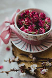 Ένα φλυτζάνι με ένα πιατάκι που γεμίζουν με τα τριαντάφυλλα και ένα ρόδινο τόξο Στοκ Εικόνα