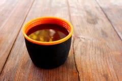 Ένα φλυτζάνι με ένα ποτό σε έναν ξύλινο πίνακα υπαίθρια στοκ εικόνα με δικαίωμα ελεύθερης χρήσης