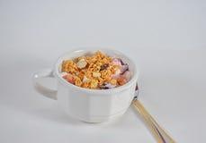 Ένα φλυτζάνι του γιαουρτιού σμέουρων με το κάλυμμα και το κουτάλι granola Στοκ Εικόνες