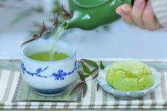 Ένα φλυτζάνι του ιαπωνικού πράσινου τσαγιού και των ιαπωνικών γλυκών Στοκ Εικόνες