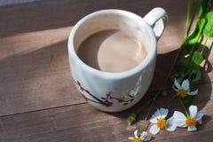 Ένα φλυτζάνι του καυτού καφέ, ρομαντικό υπόβαθρο λουλουδιών Στοκ Εικόνες