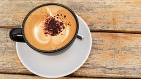 Ένα φλυτζάνι του καφέ cappuccino και του ξύλινου υποβάθρου Στοκ φωτογραφίες με δικαίωμα ελεύθερης χρήσης