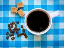 Ένα φλυτζάνι του μαύρου καφέ, των καφετιών κύβων ζάχαρης και των φασολιών καφέ Στοκ φωτογραφίες με δικαίωμα ελεύθερης χρήσης