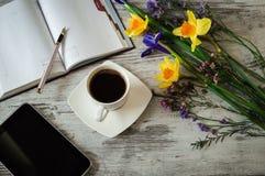 Ένα φλυτζάνι του μαύρων καφέ, της μάνδρας, της ταμπλέτας και των σημειώσεων για ένα άσπρο ξύλινο υπόβαθρο Στοκ Φωτογραφία