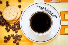 Ένα φλυτζάνι του μαύρων καφέ, των κροτίδων και των φασολιών καφέ Στοκ Εικόνες