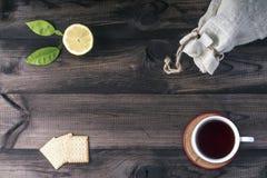 Ένα φλυτζάνι του τσαγιού με τα μπισκότα τσαγιού, ο φρέσκοι ασβέστης και το λινό τοποθετούν σε σάκκο στον ξύλινο πίνακα Στοκ Εικόνες